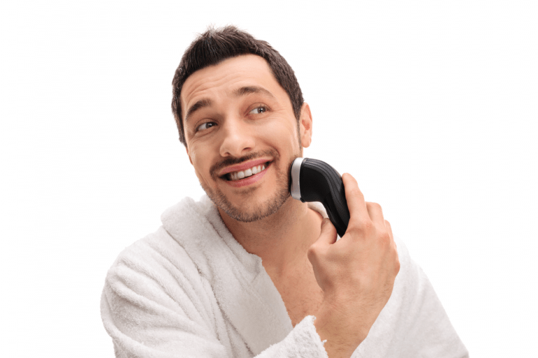 Man in a bathrobe trimming his beard with an electric razor